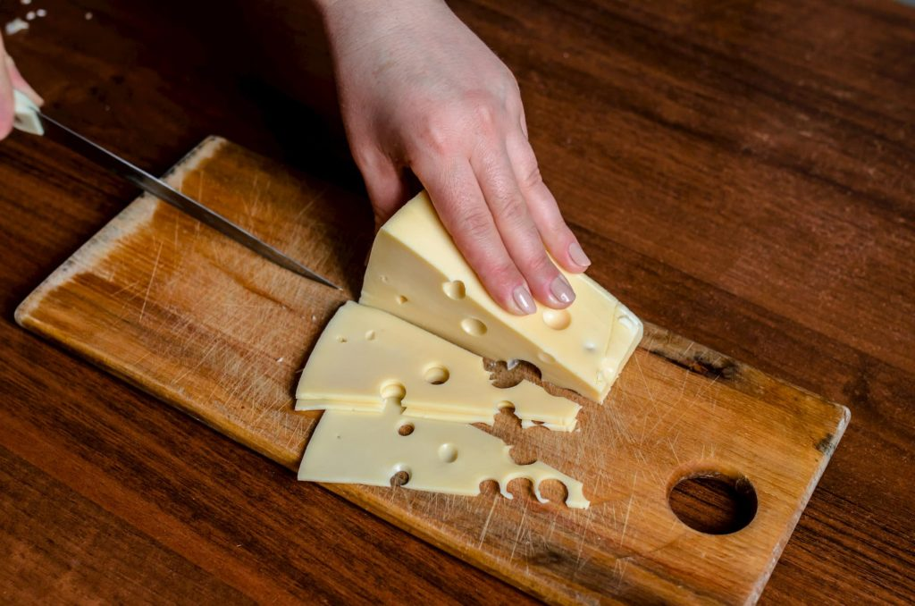 Cheese being cut on cutting board