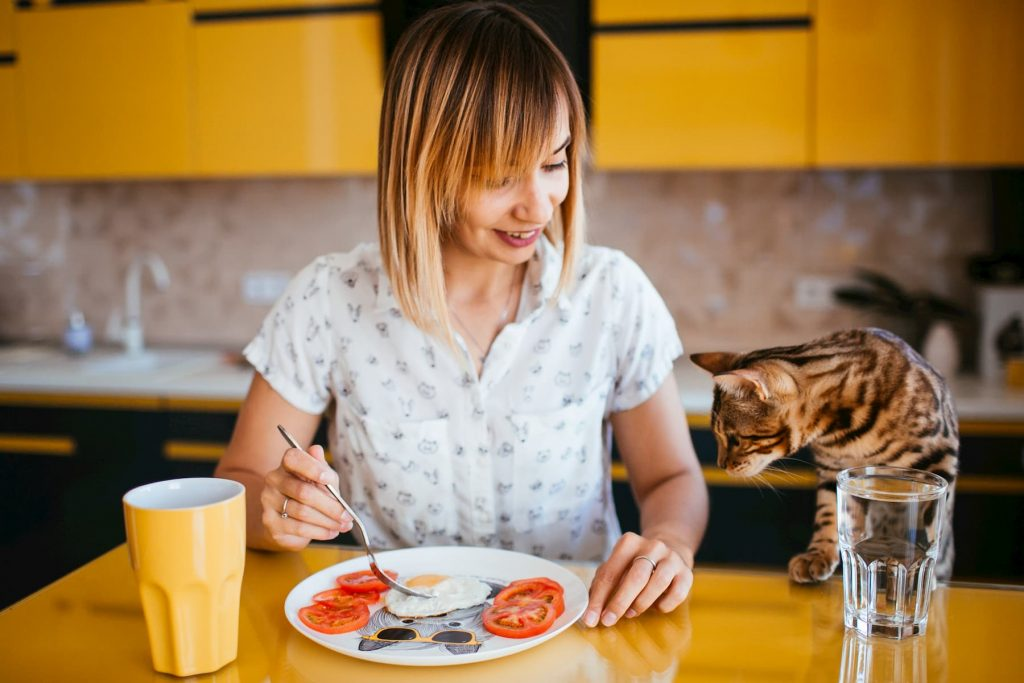Woman eating tomatoes next to a Bengal cat